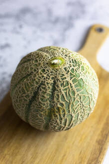 High angle view of cantaloupe with cutting board on table - GIOF06529