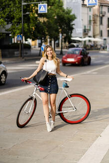 Portrait of happy young woman with racing cycle in the city - GIOF06560