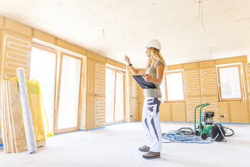 Young woman checking the construction of a new wooden house - TCF06129