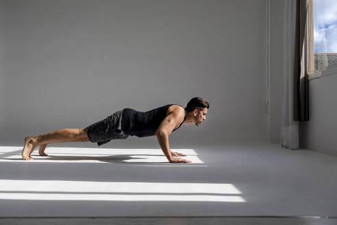 Athlete worming up in sunlit studio - MAUF02614