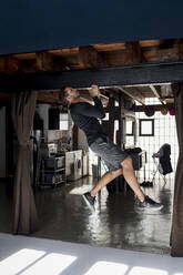 Athlete doing chin ups in his loft - MAUF02620