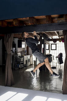 Handsome man doing workout in his loft studio home. Barcelona, Spain. - MAUF02620