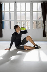 Athlete taking a break in sunlit studio, drinking water - MAUF02626