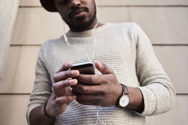 Mid adult man using smartphone and listening music - IGGF01214