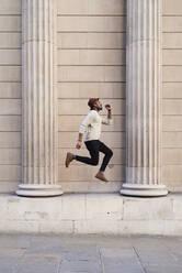Mid adult man listening music and jumping - IGGF01217