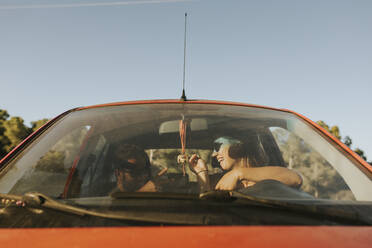 Happy couple sitting in car, talking - DMGF00056
