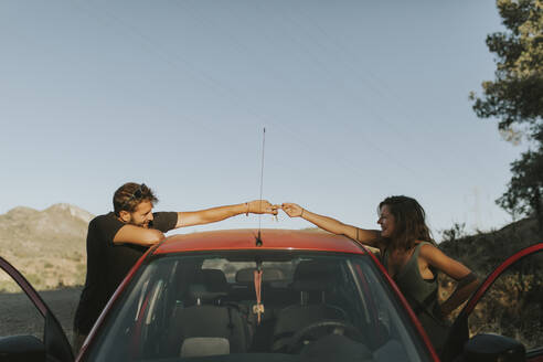 Couple exchanging car keys on a road trip - DMGF00059
