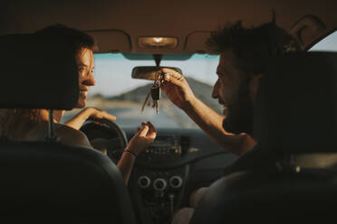 Couple exchanging car keys on a road trip - DMGF00074
