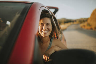 Woman on a road trip looking out of car window - DMGF00080
