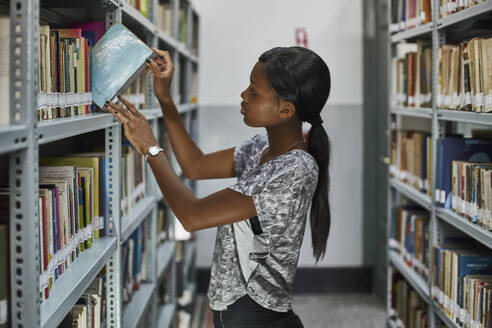 Young woman checking the books at the bookshelves at National library, Maputo, Mocambique - VEGF00387