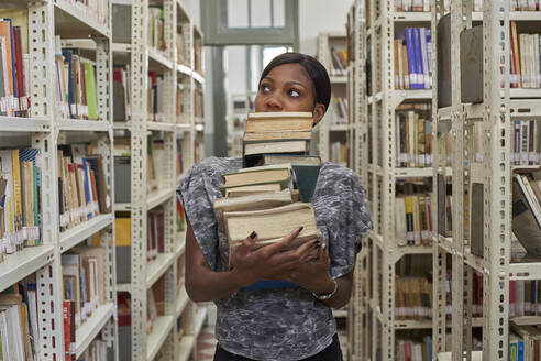 Young woman with stack of books at National library, Maputo, Mocambique - VEGF00396
