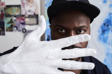 Black artist through fingers of white painted hand at his studio - IGGF01249