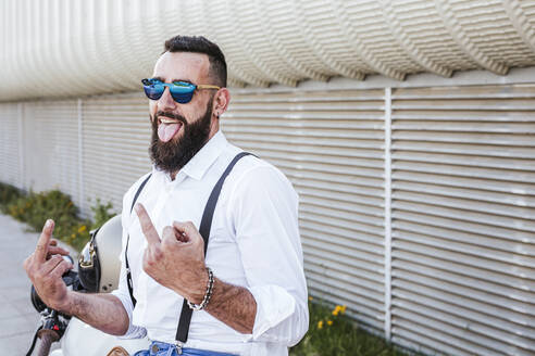 Portrait of motorcyclist with mirrored sunglasses giving the finger while sticking out tongue - LJF00285