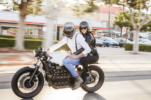 Couple riding motorbike in the city - LJF00297