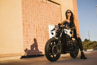 Portrait of motorcyclist on motorbike at sunset - LJF00303
