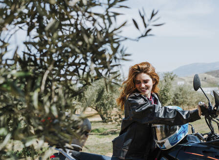 Portrait of happy redheaded woman on motorbike, Andalusia, Spain - LJF00333