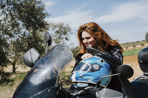 Portrait of happy redheaded woman on motorbike, Andalusia, Spain - LJF00336
