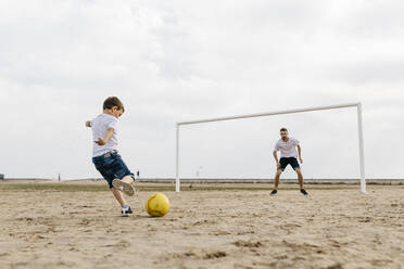 Man and boy playing soccer on the beach - JRFF03412
