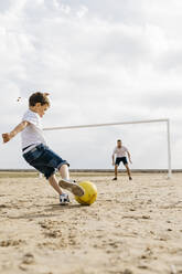 Man and boy playing soccer on the beach - JRFF03415