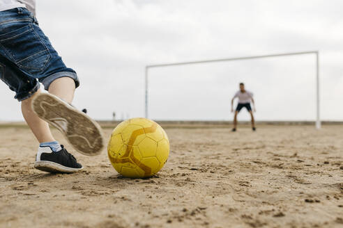 Close-up of man and boy playing soccer on the beach - JRFF03418