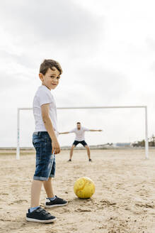 Man and boy playing soccer on the beach - JRFF03421