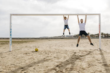 Man and boy hanging from the goal while playing soccer on the beach - JRFF03424