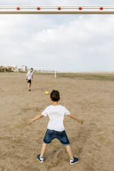 Boy and man playing soccer on the beach - JRFF03427