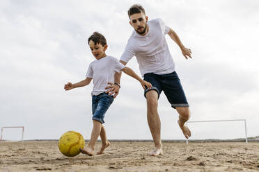 Boy and man playing soccer on the beach - JRFF03430