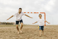 Two football players celebrating a goal on the beach - JRFF03433