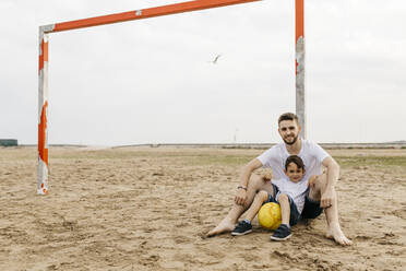Man and boy resting after soccer game on the beach - JRFF03436