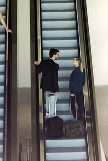 Two young business partners with baggage talking on an escalator - JSRF00377
