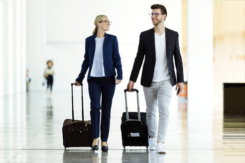 Portrait of two young business partners walking and talking through the airport hall. - JSRF00380