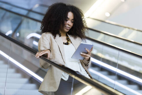 Portrait of beautiful young business woman using her digital tablet on escalator. - JSRF00383