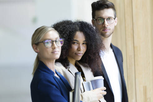 Portrait of group of business young people looking at camera in a hallway of the company. - JSRF00392