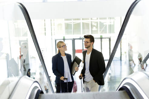 Two young business partners talking on an escalator - JSRF00398