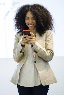Portrait of beautiful young business woman using her mobile phone in a hallway of her company. - JSRF00401