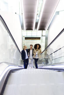 Young business people on an escalator - JSRF00419