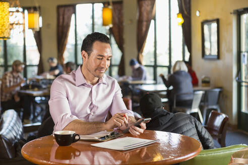 Hispanic businessman using cell phone in coffee shop - BLEF08246
