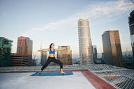 Mixed race woman practicing yoga on urban rooftop - BLEF08276