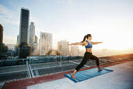 Mixed race woman practicing yoga on urban rooftop - BLEF08279