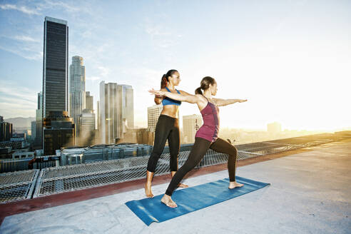 Mixed race woman practicing yoga on urban rooftop - BLEF08282