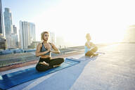 Women practicing meditating on urban rooftop - BLEF08285