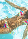 Midsection of mixed race woman swimming in swimming pool - BLEF08459