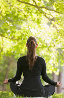 Caucasian woman practicing yoga in park - BLEF08468