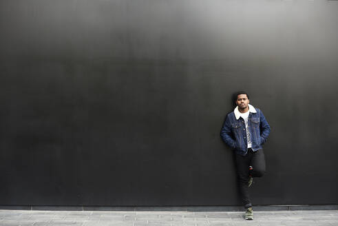 Full length Portrait of black male looking at camera against black wall. London, UK. - IGGF01267