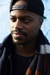 Portrait of man wearing baseball cap and scarf - IGGF01270