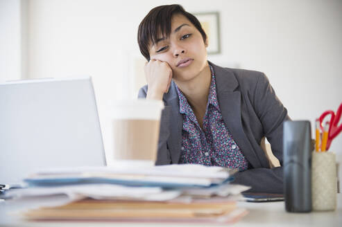 Bored mixed race businesswoman sitting at office desk - BLEF08553