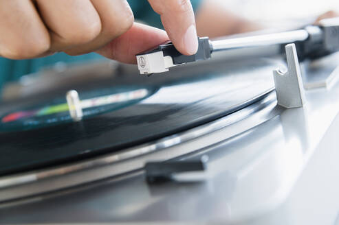 Close up of mixed race man playing vinyl record - BLEF08562