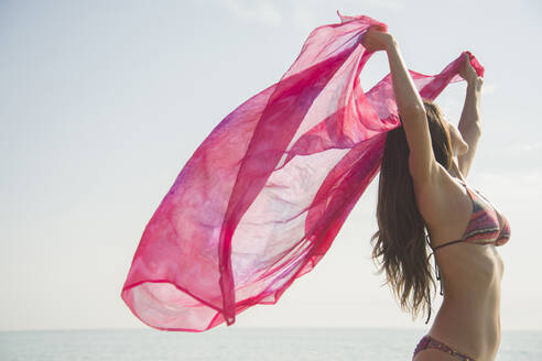 Caucasian woman holding fabric in wind at beach - BLEF08598