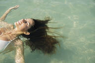 Caucasian woman floating in ocean - BLEF08607